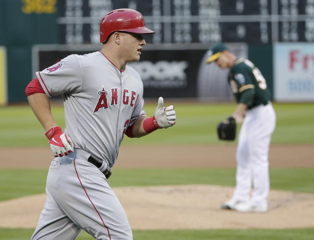 Los Angeles Angels' Mike Trout, left, rounds the bases after his solo home run off Oakland Athletics starting pitcher Sonny Gray, right, during the first inning of a baseball game on Friday, Aug. 22, 2014, in Oakland, Calif. (AP Photo/Marcio Jose Sanchez)