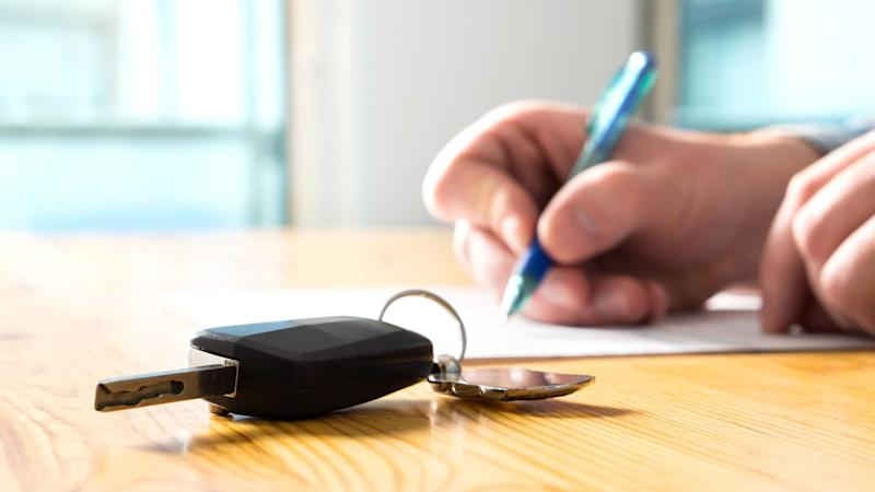 Man signing document with car keys on table