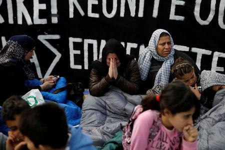 A woman cries in front of a banner announcing a hunger strike, as refugees seeking reunification with family members in Germany protest near the parliament building in Athens, Greece, November 1, 2017. REUTERS/Alkis Konstantinidis
