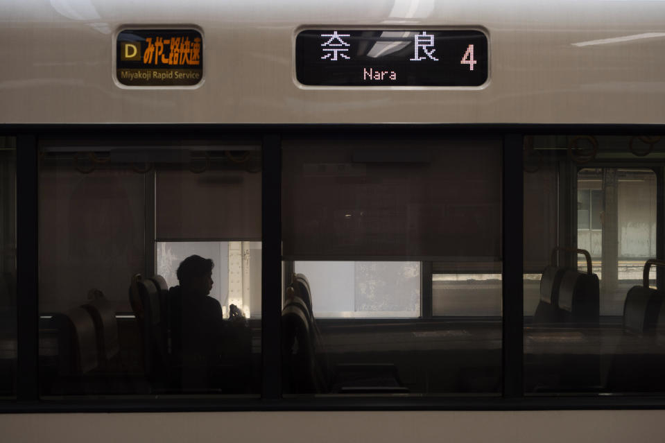 A man is silhouetted while sitting in a train bound for Nara at Kyoto Station in Kyoto, Japan on March 17, 2020. (AP Photo/Jae C. Hong)