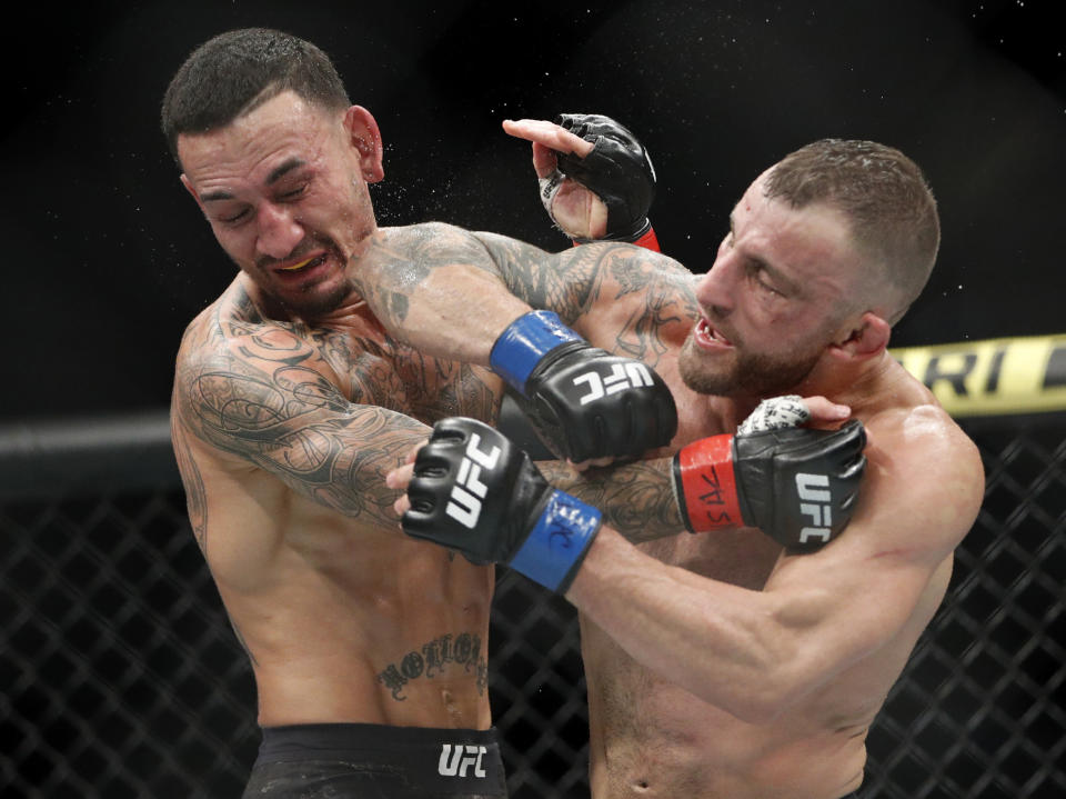 Alexander Volkanovski lands an elbow to Max Holloway in a mixed martial arts featherweight championship bout at UFC 245, Saturday, Dec. 14, 2019, in Las Vegas. (AP Photo/John Locher)