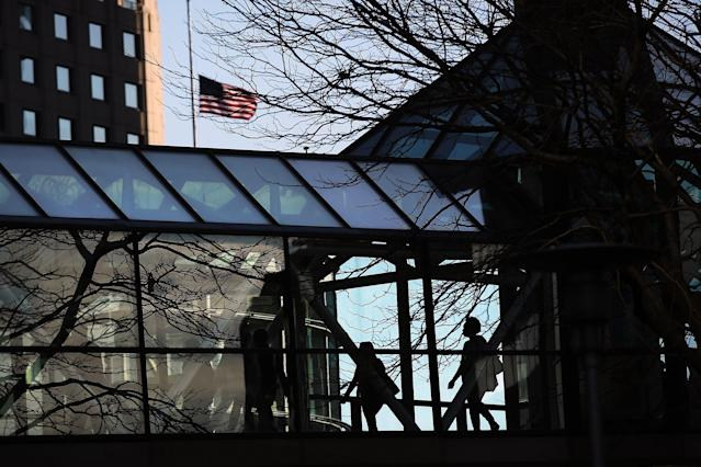 BOSTON, MA - APRIL 17: People walk to work past a flag flying at half-staff near the scene of twin bombings at the Boston Marathon on April 17, 2013 in Boston, Massachusetts. The explosions, which occurred near the finish line of the 116-year-old Boston race on April 15, resulted in the deaths of three people with more than 170 others injured. Security has been heightened across the nation as the search continues for the person or people behind the bombings. (Photo by Spencer Platt/Getty Images)