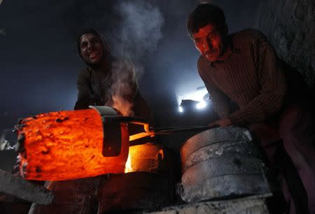 Workers pour melted copper in a mould to make utensils and accessories inside a workshop in Srinagar