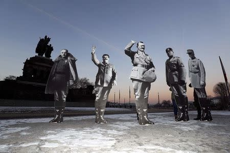 """Members of the campaigning community Avaaz placed life-size cardboards, depicting Benito Mussolini, Adolf Hitler, Josef Stalin, Francisco Franko and Philippe Petain in front of the Kaiser Wilhelm monument at the Deutsches Eck (""""German Corner"""") to protest against a European far-right leaders meeting, in Koblenz, Germany, January 21, 2017.      REUTERS/Kai Pfaffenbach"""
