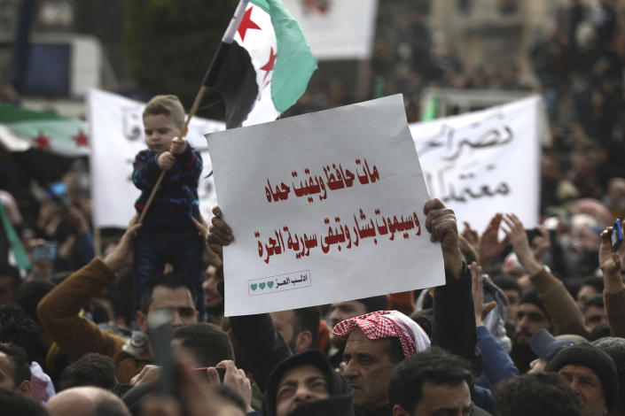 """An anti-Syrian government protester holds up an Arabic placard that reads: """"Hafez died and Hama stayed and Bashar will die and Syria will stay free,"""" to mark 10 years since the start of a popular uprising against President Bashar Assad's rule, that later turned into an insurgency and civil war, In Idlib, the last major opposition-held area of the country, in northwest Syria, Monday, March 15, 2021. (AP Photo/Ghaith Alsayed)"""
