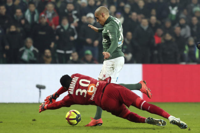 Saint-Etienne's Wahbi Khazri, right, challenges for the ball with Marseille's goalkeeper Steve Mandanda during their French League One soccer match in Saint-Etienne, central France, Wednesday, Jan. 16, 2019. (AP Photo/Laurent Cipriani)