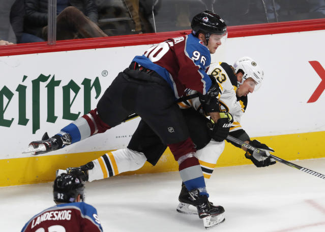 Colorado Avalanche right wing Mikko Rantanen, left, checks Boston Bruins left wing Brad Marchand, who was trying to retrieve the puck during the first period of an NHL hockey game Wednesday, Nov. 14, 2018, in Denver. (AP Photo/David Zalubowski)