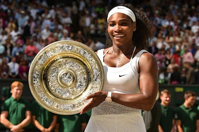 US player Serena Williams celebrates with the winner's trophy, the Venus Rosewater Dish, after her women's singles final victory over Spain's Garbine Muguruza on day twelve of the 2015 Wimbledon Championships at The All England Tennis Club in Wimbledon, southwest London, on July 11, 2015. Williams won 6-4, 6-4. RESTRICTED TO EDITORIAL USE -- AFP PHOTO / LEON NEAL (AFP Photo/Leon Neal)