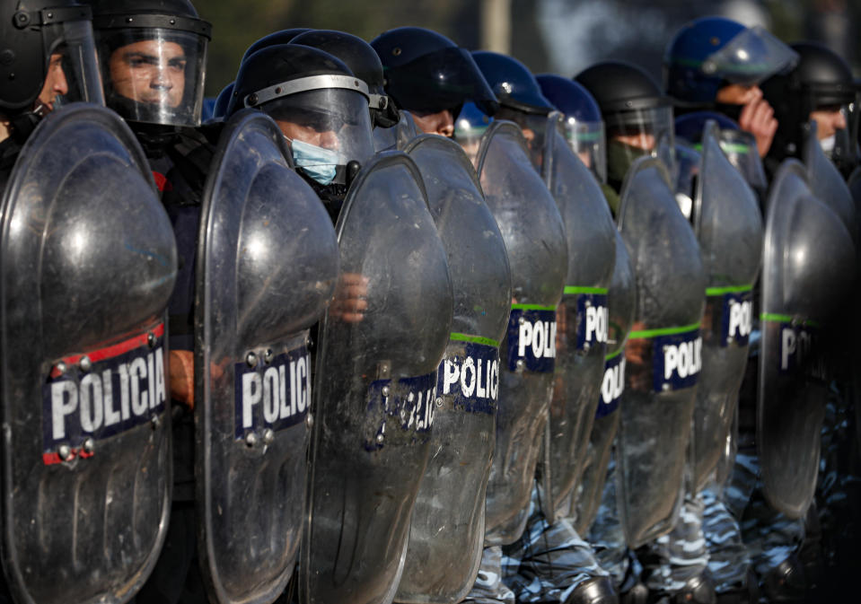 Police carry out evictions at a squatters camp in Guernica, Buenos Aires province, Argentina, Thursday, Oct. 29, 2020. A court ordered the eviction of families who are squatting here since July, but the families say they have nowhere to go amid the COVID-19 pandemic. (AP Photo/Natacha Pisarenko)