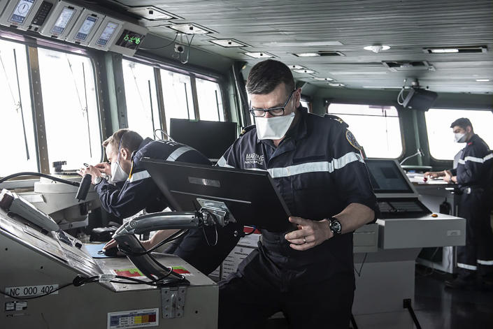 This photo provided Saturday April 10, 2020 by the French Navy (Marine Nationale) shows sailors wearing face masks aboard the French aircraft carrier Charles de Gaulle, Thursday April 8, 2020 in the Atlantic Ocean. France's only aircraft carrier has confirmed 50 cases of the new virus aboard and is heading back to port. Three of those aboard the Charles de Gaulle with the virus have been flown to French hospitals for treatment, the French military said in a statement Friday .The new coronavirus causes mild or moderate symptoms for most people, but for some, especially older adults and people with existing health problems, it can cause more severe illness or death. (Y. Bisson/Marine Nationale via AP)