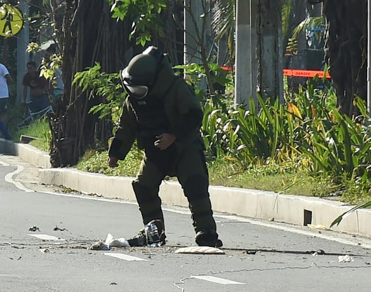 A police bomb disposal expert works to defuse a bomb found in a rubbish bin near the US embassy in Manila on November 28, 2016