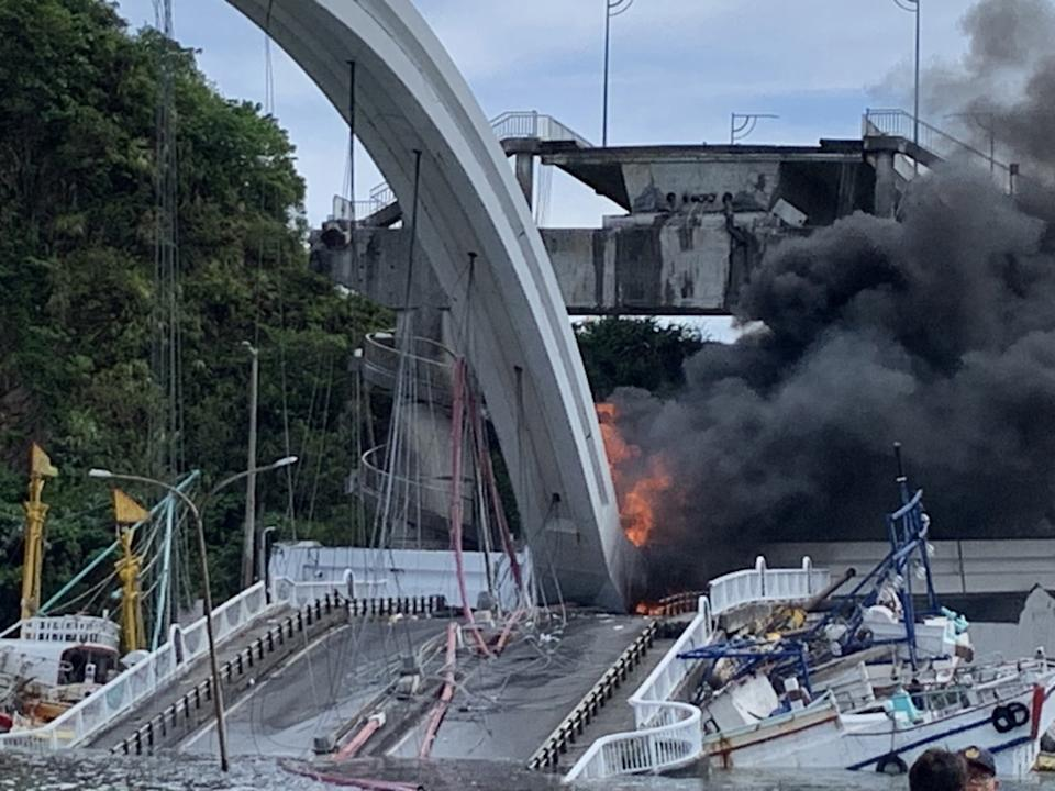 Fire can be seen coming from the bridge collapse.