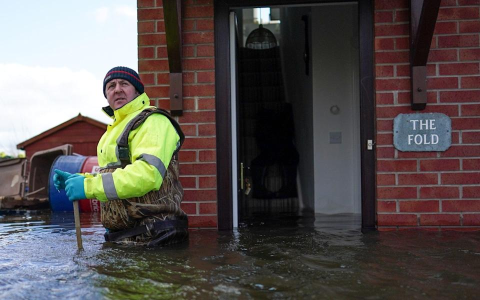 Steve Lamb stands by the door of his father's home as he prepares to enter as flooding affects homes and businesses after the River Aire bursts its banks on March 01, 2020 in East Cowick, England - Getty