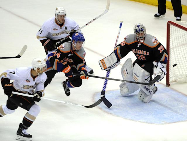 New York Islanders' Thomas Hickey (14) chases the puck away between Anaheim Ducks' Andrew Cogliano (7) and Saku Koivu (11) as Islanders goalie Evgeni Nabokov defends the net during the first period of an NHL hockey game Saturday, Dec. 21, 2013, in Uniondale, N.Y. (AP Photo/Kathy Kmonicek)