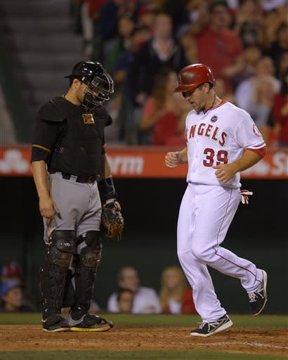 Los Angeles Angels' J.B. Shuck, right, scores on a single by Mike Trout as Pittsburgh Pirates catcher Russell Martin looks on during the seventh inning of their baseball game, Saturday, June 22, 2013, in Anaheim, Calif. (AP Photo/Mark J. Terrill)