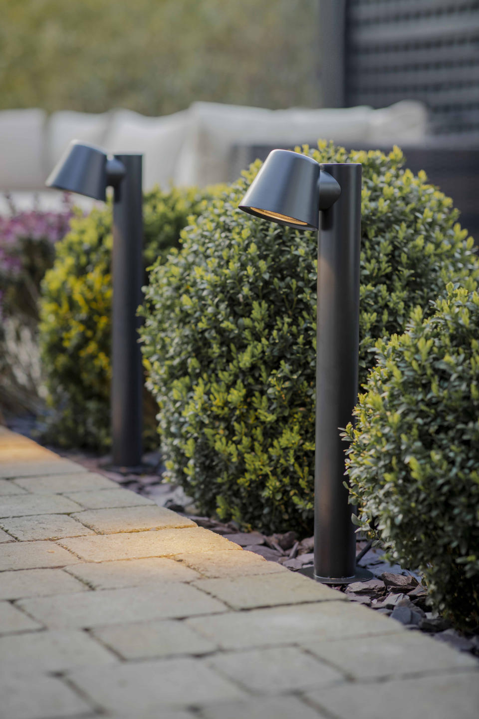 pathway lined with small post lights in a flowerbed