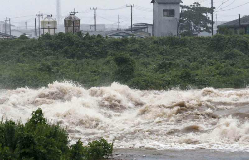 In this Wednesday, July 3, 2019, photo, a river is swollen with the heavy in Miyakonojo, Miyazaki prefecture, western Japan. Japanese authorities on Wednesday directed more than 1 million residents in parts of the southern main island of Kyushu to evacuate to designated shelters as heavy rains batter the region, prompting fears of landslides and widespread flooding.(Kyodo News via AP)