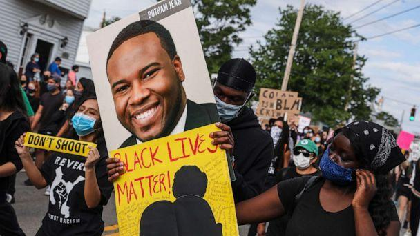 PHOTO: A demonstrator holds a sign for Botham Jean while marching during a demonstration, June 9, 2020, in Revere, Mass., for George Floyd and other Black Americans killed at the hands of law enforcement.  (Erin Clark/The Boston Globe via Getty Images, FILE)