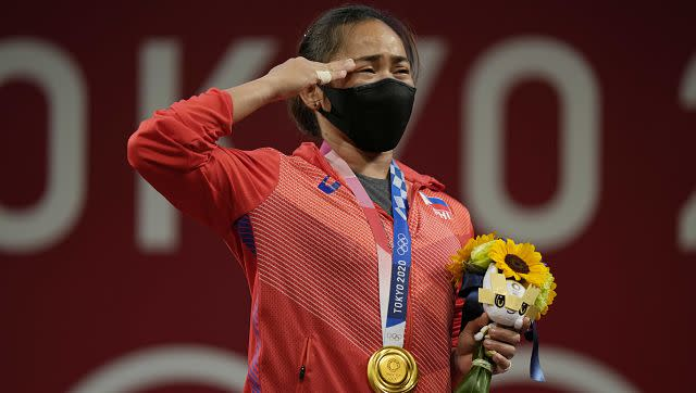 Hidilyn Diaz of Philippines gestures on the podium as she listen to the national anthem after winning the gold medal in the women's 55kg weightlifting event. AP