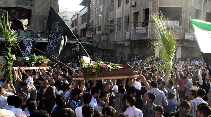In this Saturday, April 21, 2012 photo, Syrian mourners carry the bodies of an infant, Adam al Najjar, and Free Syrian Army fighter, Mowaffaq al Nablsi, 42, during their funeral in Douma, a suburb of Damascus, Syria. Syrian troops stormed and shelled districts in a suburb of the capital Damascus Sunday, activists said, a day after the Security Council voted to expand the number of U.N. truce monitors from 30 to 300 in hopes of salvaging an international peace plan marred by continued fighting between the military and rebels. (AP Photo)