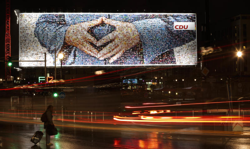 In this photo taken with a long shutter release, a huge election banner of the ruling Christian democratic Union party showing the hands of Chancellor Angela Merkel in a typical position is displayed near the central station in Berlin on Monday, Sept 2, 2013. Germany faces general election on Sept. 22, 2013 and Chancellor Angela Merkel runs for re election. (AP Photo/Markus Schreiber)
