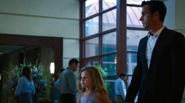 Kevin wears a suit and walks through a hotel lobby holding hands with a little girl