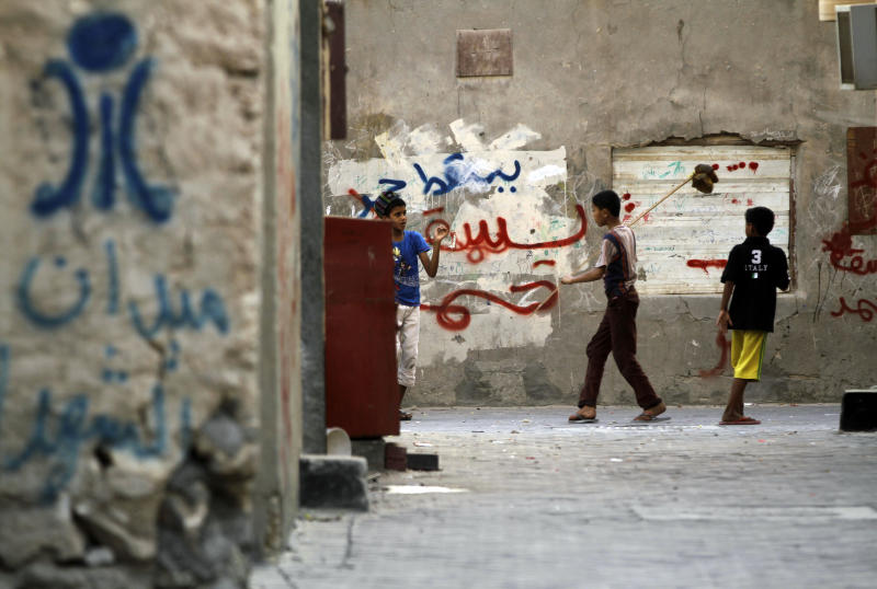 "Bahraini children play in an alley spray-painted with anti-government graffiti in Malkiya, Bahrain, on Monday, Aug. 6, 2012. At left above the words ""Martyrs Square,""  is a painted image of the since-demolished monument that stood at the site of huge Spring 2011 pro-democracy protests. Back wall graffiti includes ""down Hamad,"" referring to Bahrain's king. (AP Photo/Hasan Jamali)"