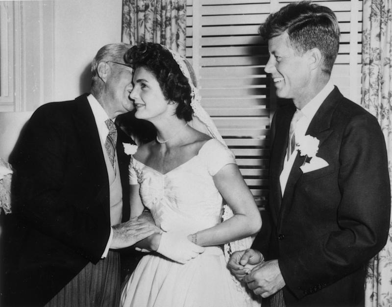 Joseph Kennedy (1888 - 1969) whispers to his new daughter-in-law Jacqueline Bouvier (1929 - 1994) on her wedding day as her husband John F. Kennedy (1917 - 1963) looks on, smiling, Newport, Rhode Island, September 12, 1953. (Photo by Hulton Archive/Getty Images)