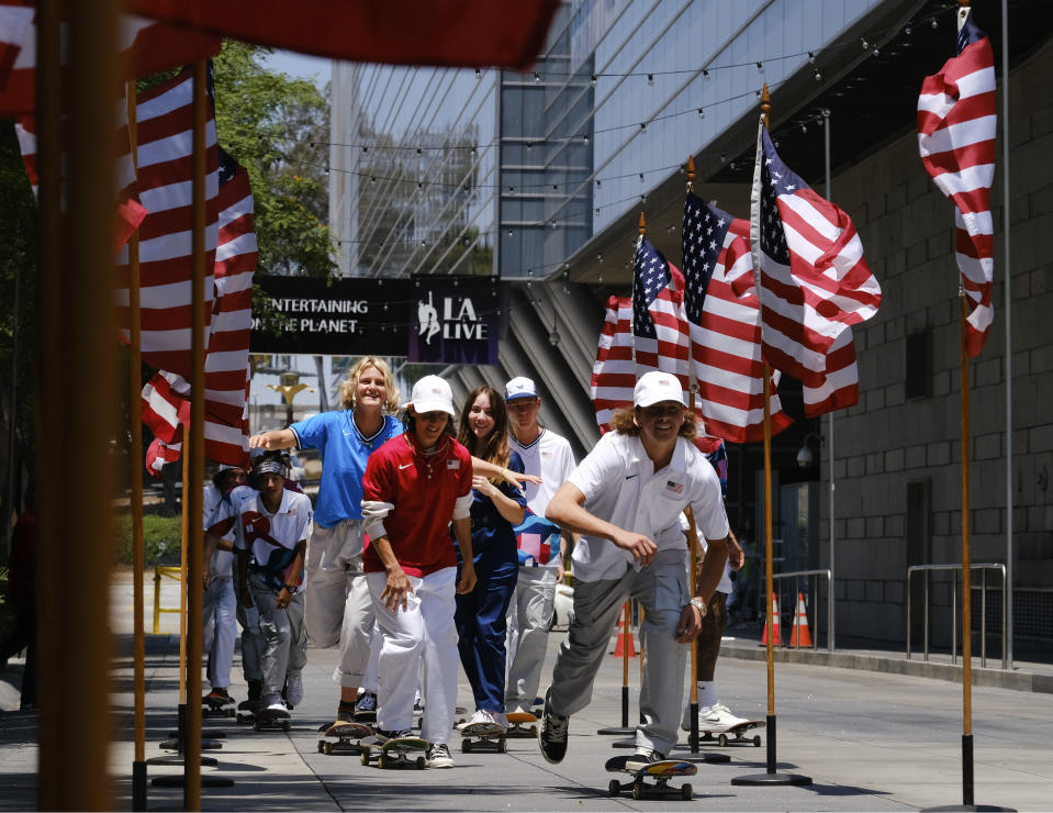 Members of the first U.S. Olympic skateboarding team arrive on their boards for a news conference in downtown Los Angeles on Monday, June 21, 2021. The Olympic skateboarding team was introduced in Southern California, where the sport was invented roughly 70 years ago. Skateboarding is an Olympic sport for the first time in Tokyo, and the Americans are expected to be a strong team. (AP Photo/Richard Vogel)