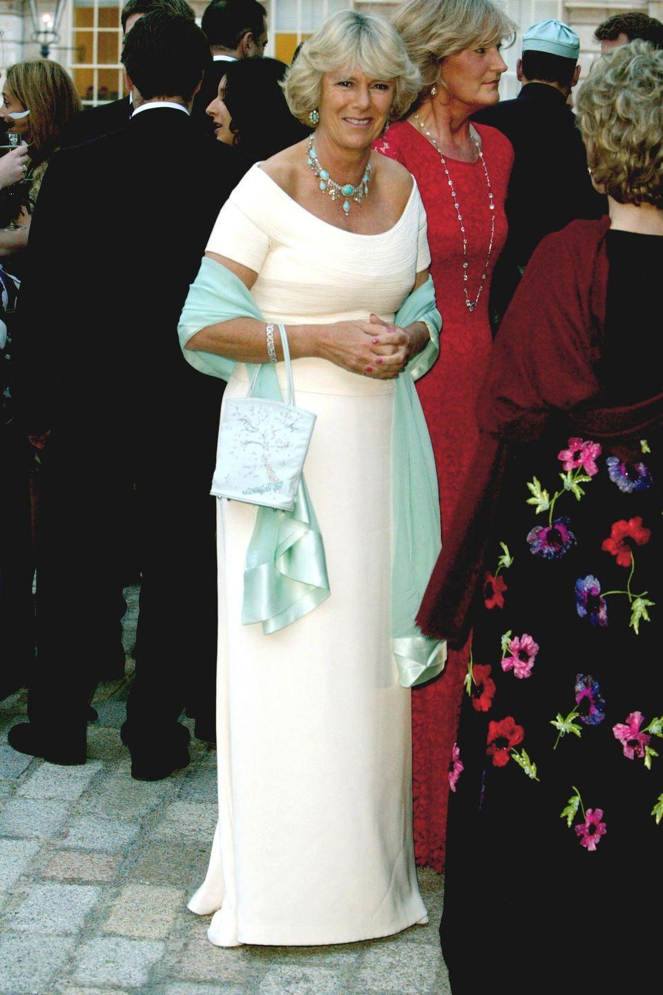 <p>For a summer fete at Somerset House in London, Camilla wore a long, shoulder-sweeping cream dress with pops of turquoise. </p>