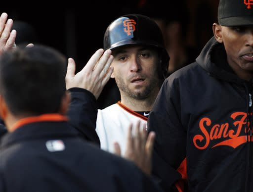 San Francisco Giants' Marco Scutaro is greeted in the dugout after scoring on a Buster Posey single during the first inning of a baseball game against the Atlanta Braves, Thursday, May 9, 2013, in San Francisco. (AP Photo/George Nikitin)