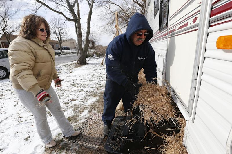 Anthony Cavallo, right, and his wife Jeanne Cavallo use hay to insulate their trailer in preparation for a cold night, Wednesday, Jan. 23, 2013, in Union Beach, N.J. The Cavallo's had to buy the trailer out of pocket and place it next to their home damaged by Superstorm Sandy because they've yet to receive storm aid. Cold weather is bringing extra worries to residents of the areas hit by Sandy. The deep freeze will continue into Thursday and Friday. There's a chance of snow Friday afternoon and evening, but accumulations are expected to be minor. (AP Photo/Julio Cortez)