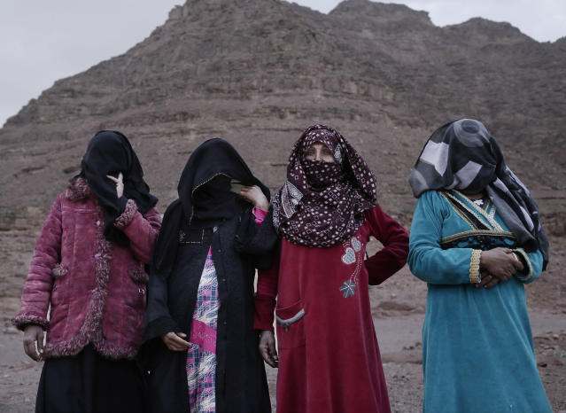 In this March 30, 2019 photo, the first female Bedouin guides, from right, Selima, Umm Yasser, Umm Soliman, and Aicha, pose for a photograph in Wadi Sahw, Abu Zenima, in South Sinai, Egypt. Four Bedouin women are for the first time leading tours in Egypt's Sinai Peninsula, breaking new ground in their deeply conservative community, where women almost never work outside the home or interact with outsiders. The women guide groups of female tourists through the stunning mountain landscapes, part of a Bedouin-led project of hiking tours in southern Sinai aiming to benefit a population that often complains it is left out of major tourism development. (AP Photo/Nariman El-Mofty)