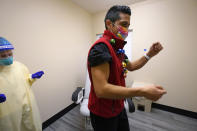 Dr. Dakotah Lane, a member of the Lummi Nation, right, does a brief dance after receiving a COVID-19 vaccination from registered nurse Alyssa Lane, Thursday, Dec. 17, 2020, at the Chinook Clinic on the Lummi Reservation, near Bellingham, Wash. The Native American tribe began rationing its first 300 doses of vaccine as it fights surging cases with a shelter-in-place order. (AP Photo/Elaine Thompson)