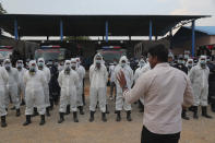 Director Disaster Response Force of Telangana State Vishwajeet Kampati gives instructions to members of his team prior to spraying disinfectants as a precautionary measure against COVID-19 in Hyderabad, India, Friday, March 20, 2020. For most people, the new coronavirus causes only mild or moderate symptoms. For some it can cause more severe illness. (AP Photo/Mahesh Kumar A.)