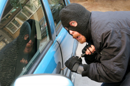 Masked man breaking into car