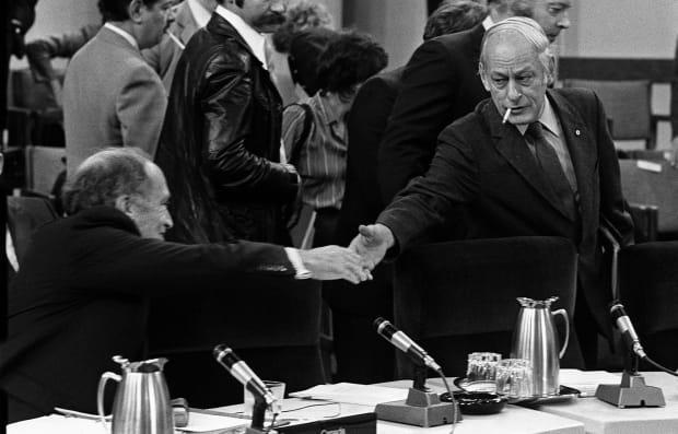 Prime Minister Pierre Trudeau stretches to shake hands with  Quebec Premier René Lévesque at the start of the meeting of the first ministers in Ottawa Nov. 2, 1981.At this set of talks, the provinces made their support for constitutional reforms contingent on the inclusion of a 'notwithstanding clause.'