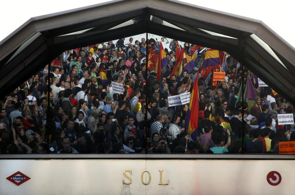Protesters are reflected in the glass of an entrance to a metro station at Madrid's Puerta del Sol square during an anti-monarchist demonstration following the announcement of the abdication of Spain's King Juan Carlos June 2, 2014. King Juan Carlos said on Monday he would abdicate in favour of his son Prince Felipe, aiming to revive the scandal-hit monarchy at a time of economic hardship and growing discontent with the wider political elite. REUTERS/Juan Medina (SPAIN - Tags: ROYALS CIVIL UNREST)