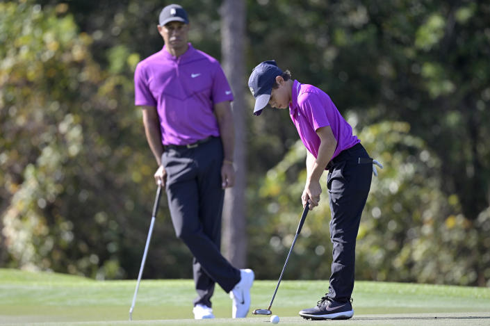 Tiger Woods watches as his son Charlie sinks a putt on the first green during the first round of the PNC Championship golf tournament, Saturday, Dec. 19, 2020, in Orlando, Fla. (AP Photo/Phelan M. Ebenhack)
