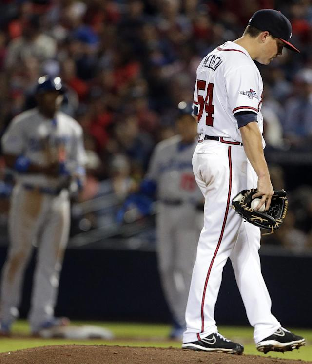 Atlanta Braves starting pitcher Kris Medlen, right, walks to Atlanta Braves manager Fredi Gonzalez as he is relieved in the fifth inning of Game 1 of the National League Division Series against the Los Angeles Dodgers, Thursday, Oct. 3, 2013, in Atlanta. (AP Photo/David Goldman)
