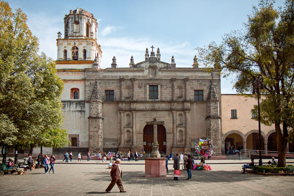 Mexico City, Mexico - December 2, 2017: Visitors and locals alike gather in the town square around the Coyoacan Cathedral, located in the picturesque town square of Coyoacan, one of the 16 boroughs of Mexico City.