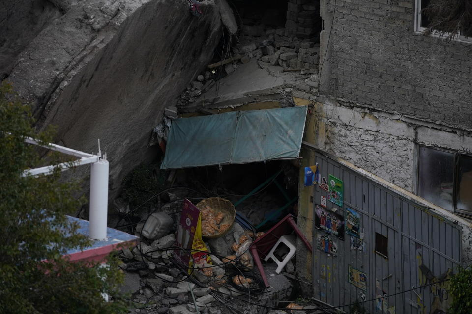 A vendor's products lay amid the debris amid a three-story pile of rocks in Tlalnepantla, on the outskirts of Mexico City, when a mountain gave way on Friday, Sept. 10, 2021, plunging rocks the size of small homes onto a densely populated neighborhood. (AP Photo/Eduardo Verdugo)
