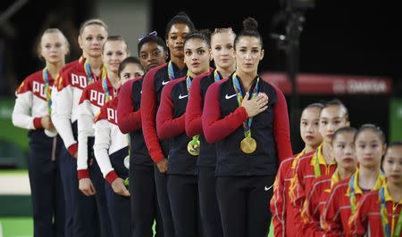 2016 Rio Olympics - Artistic Gymnastics - Final - Women's Team Final - Rio Olympic Arena - Rio de Janeiro, Brazil - 09/08/2016. Simone Biles (USA) of USA, Gabrielle Douglas (USA) of USA (Gabby Douglas), Laurie Hernandez (USA) of USA, Madison Kocian (USA) of USA, Alexandra Raisman (USA) of USA (Aly Raisman) sing their national anthem with their gold medals on the podium after winning the women's team final. On right are bronze medallists China, with silver medallists Russia at the back. REUTERS/Dylan Martinez