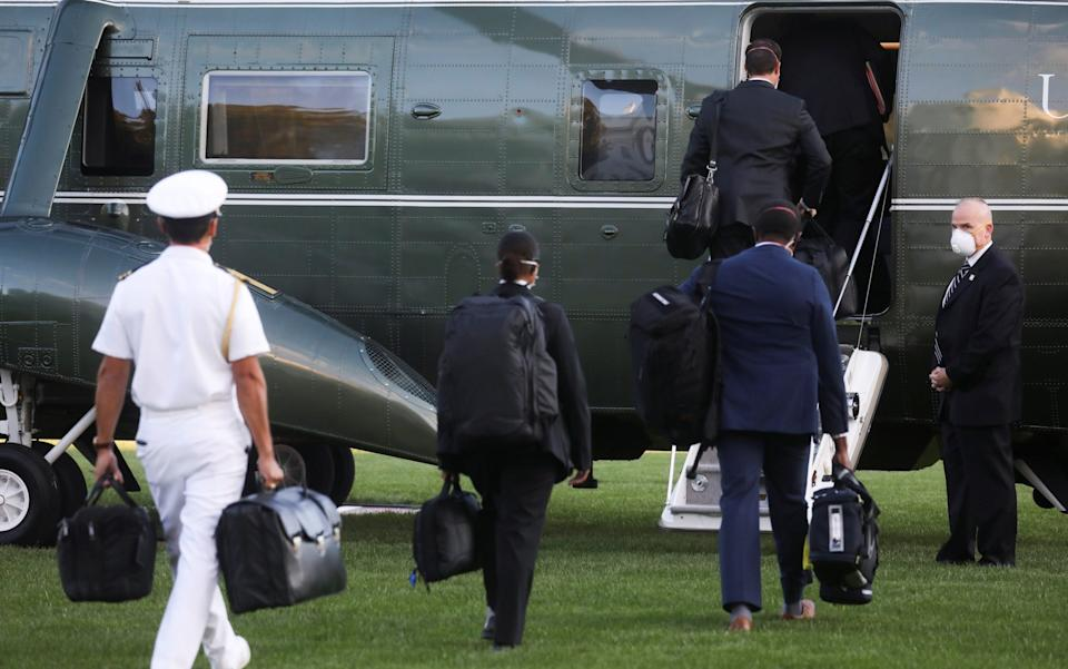 """White House aides, including the military aide carrying the nuclear launch codes known as """"the nuclear football,"""" follow U.S. President Donald Trump as he boards the Marine One - REUTERS"""