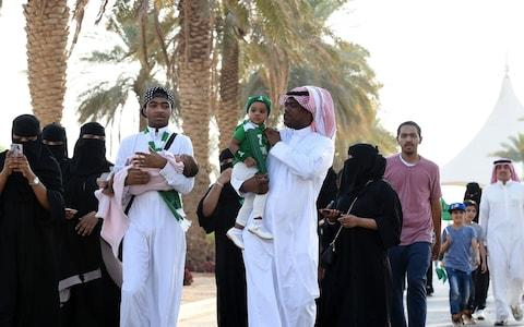 Saudi families arrive outside a stadium to attend an event in the capital Riyadh - Credit: AFP