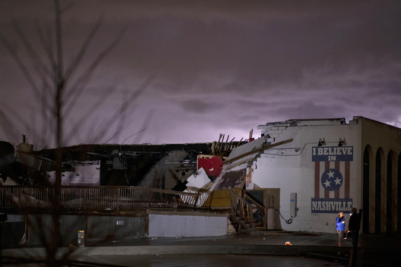 NASHVILLE, TN - MARCH 03:  A television news crew works in front of a mural on heavily damaged The Basement East in the East Nashville neighborhood as lightning strikes in the background on March 3, 2020 in Nashville, Tennessee. A tornado passed through Nashville just after midnight leaving a wake of damage in its path including two people killed in East Nashville. (Photo by Brett Carlsen/Getty Images)
