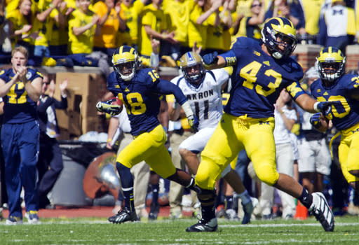 Michigan defensive back Blake Countess (18) returns an interception a pass intended for Akron wide receiver Zach D'Orazio (11), as defensive lineman Chris Wormley (43) prepares to block, in the second quarter of an NCAA college football game, Saturday, Sept. 14, 2013, in Ann Arbor, Mich. (AP Photo/Tony Ding)