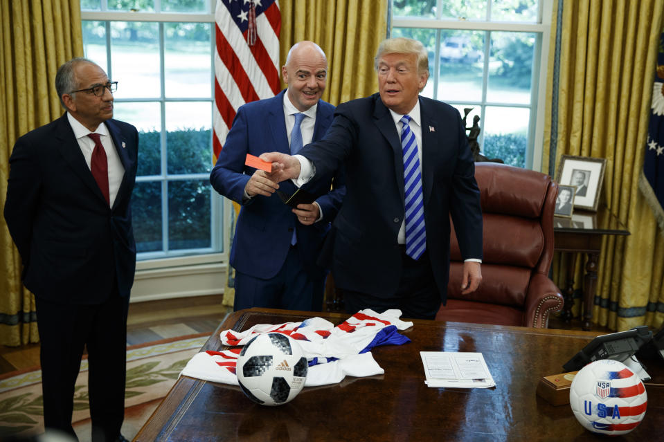 President Donald Trump handed out a red card to reporters during a meeting with the FIFA president. (AP Photo)