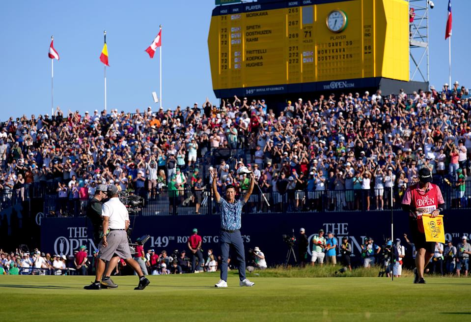 Collin Morikawa celebrates on front of packed grandstands around the 18th green (PA Wire)