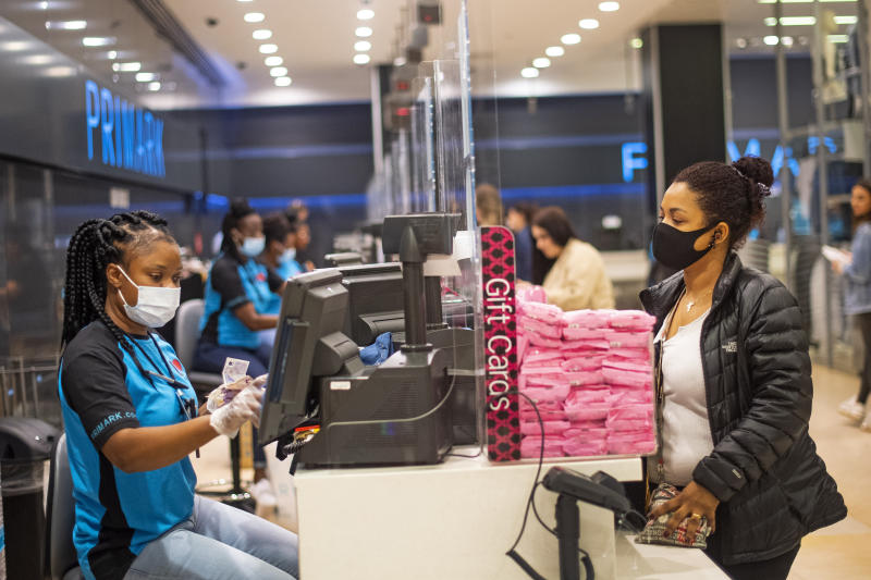 A staff member and customer wear face masks, with a protective screen at the till point, inside Primark in Oxford Street, London as non-essential shops in England open their doors to customers for the first time since coronavirus lockdown restrictions were imposed in March.